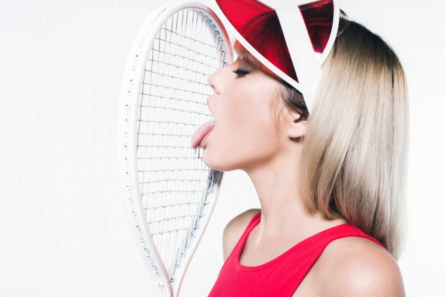 Sexy woman licking a tennis racquet
